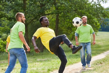 Young team plays football together on a sports festival or team event