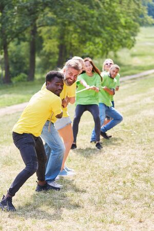 Two teams measure forces in tug of war on teambuilding event