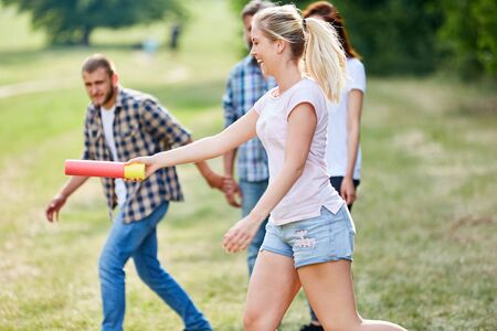 Young woman hands the baton in a relay race at the teambuilding workshop