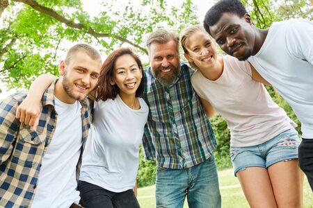 Szczęśliwa wielokulturowa grupa młodych ludzi lub przyjaciół w naturze