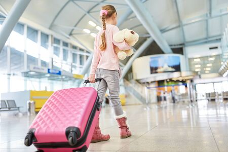 Girl as a passenger with suitcase and stuffed animal in the airport terminal travels alone Imagens
