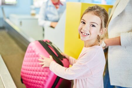 Little girl happily smiles at the check-in desk while bagging suitcase