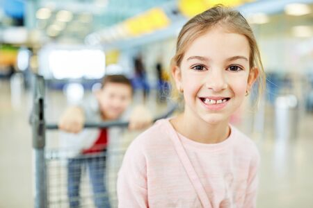 Happy girl is looking forward to the air travel in the summer vacation in the airport terminal