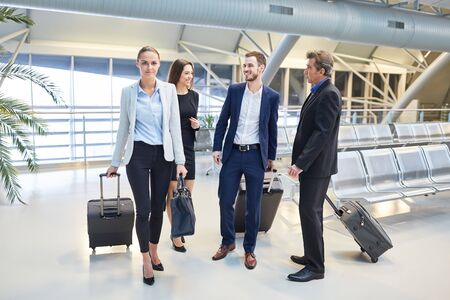 Group of business people with luggage on business trip on arrival in airport terminal