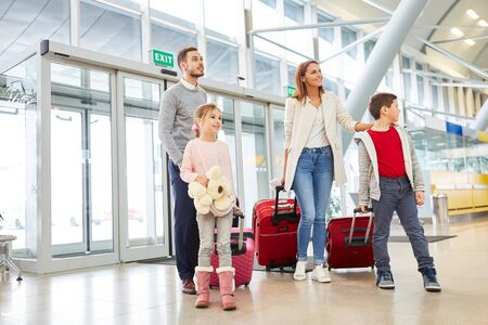 Family and two children fly on vacation and look around the airport terminal Zdjęcie Seryjne