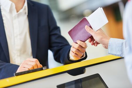 Service Agent checks a passengers passport at the airport check-in counter