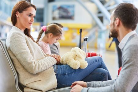 Family and two children are waiting in the rest area for the departure in the airport terminal