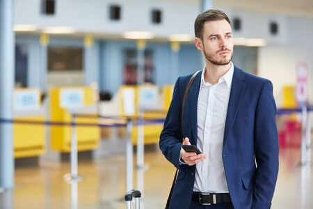 Young businessman with smartphone on mission in airport terminal on arrival