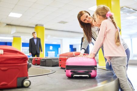 Mother and children as passengers look for their suitcases on the luggage rack in the airport terminal