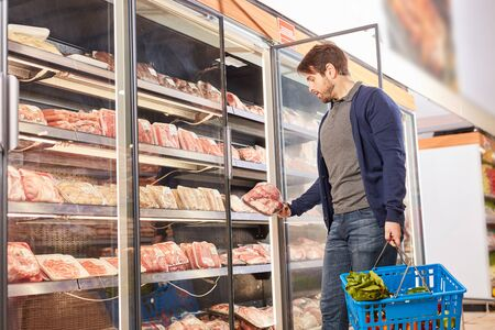 Young man with shopping basket at the freezer while buying meat in supermarket Stock fotó