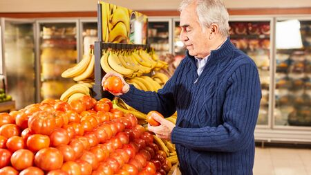 Senior as a customer while shopping fresh organic tomatoes in the vegetable section