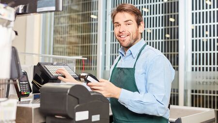 Cheerful young man as a cashier at the cash register Stock Photo