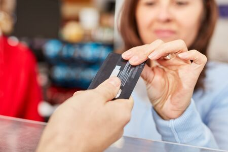 Customer with credit card or customer card during cashless payment