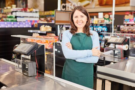 Woman in green apron as a cashier in the supermarket or retail business