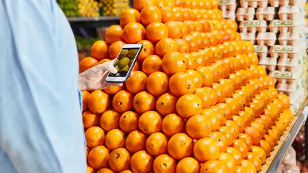 Customer uses smartphone app when buying fresh fruit in the supermarket Stock fotó