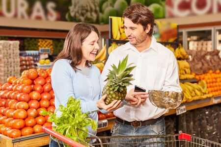 Couple shopping at the supermarket uses smartphone app for product comparison