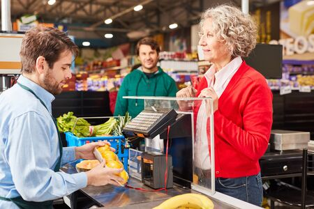 Customer at checkout in supermarket looks at cashier at work
