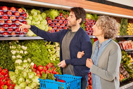 Couple at the grocery shopping on the shelf in the vegetable department in the supermarket