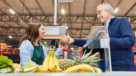 Customer pays fruit shopping at the supermarket cashier at friendly cashier