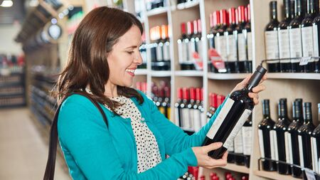 Young woman as a customer in the supermarket with a bottle of red wine in the hand