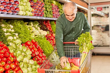 Senior as a customer packs fresh vegetables in his shopping cart in the supermarket