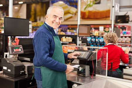 Friendly cashier with green apron at the cash register in the supermarket