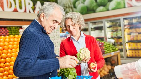 Senior couple shopping for vegetables in the vegetable section in the supermarket