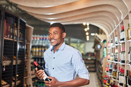 African man with a bottle of red wine in the wine shop in the supermarket