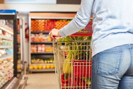 Customer pushes cart with food by aisle in supermarket