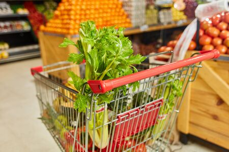 Full shopping cart with many fresh foods in the supermarket Stock fotó