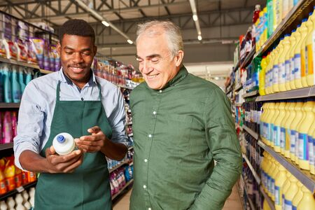 African seller at a customer consultation and recommendation in the supermarket Stock Photo