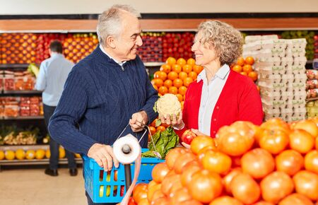 Couple of seniors as a vegetarian is buying organic vegetables for healthy eating in the supermarket Stock fotó