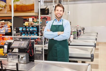 Smiling cashier or salesman in green apron at the supermarket cashier Banco de Imagens