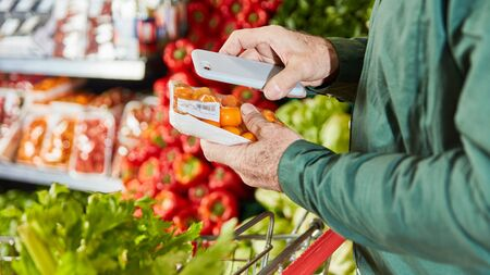 Customer scans pack of food with smartphone app for price comparison Stock fotó