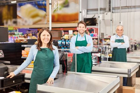 Friendly salesman colleague team with apron at checkout in supermarket