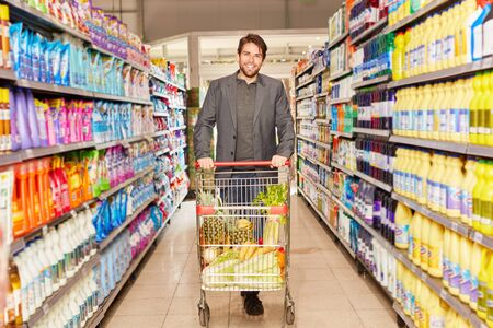 Smiling man pushes a shopping cart with groceries at the discount store