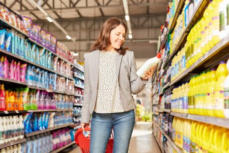 Woman as a customer reads the label on a product in the supermarket or discounter