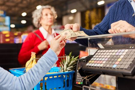 Customer gives cashier a cash receipt as payment at the supermarket cashier