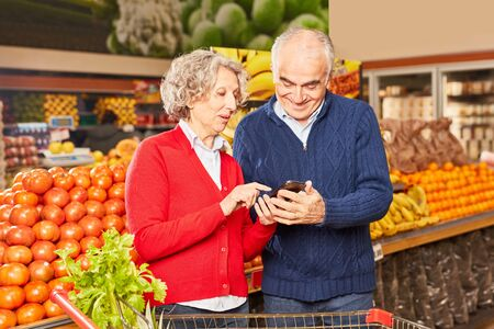 Couple of seniors as consumers uses smartphone app for price comparison