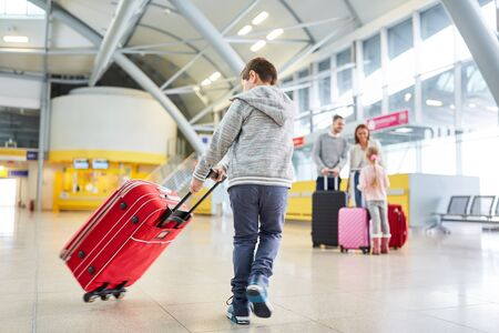 Boy plays with a suitcase in the airport terminal and looks forward to the flight on vacation Zdjęcie Seryjne