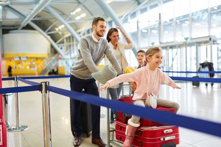 Happy family and two kids are having fun in airport terminal just before departure