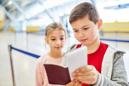 Boy with passport and sister in airport terminal fly together on vacation Zdjęcie Seryjne