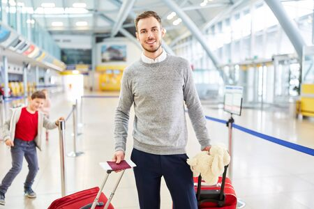 Smiling man as a passenger with luggage in the airport. Terminal looks happy on arrival Imagens
