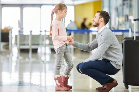 Father and daughter in the airport terminal travel together on vacation