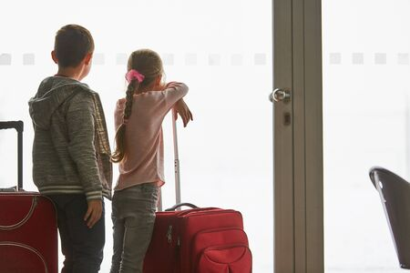Two children in the airport terminal look curiously through a window on the runway