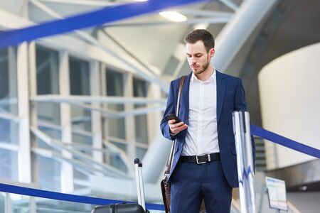 Young business man on business trip looks at his smartphone in airport terminal Imagens