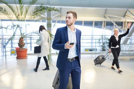 Young businessman using smartphone in a hurry in airport terminal before departure