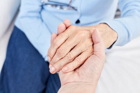 Female nursing assistant holds the hand of a senior citizen as support and comfort