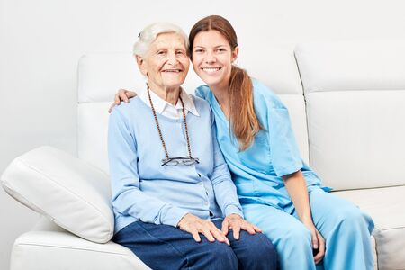 Smiling nursing assistant and happy senior woman are sitting together on the sofa