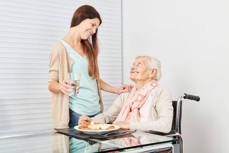 Senior nurse gets a lunch from nursing assistant Stockfoto